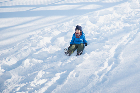 Cute Asian child sliding on snow in the park Imagens