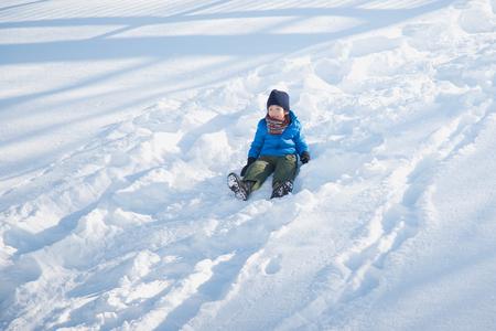 Cute Asian child sliding on snow in the park Stock fotó