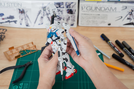 BANGKOK, THAILAND - July 30, 2018 :Hands of Asian man hand build Gundam plastic model on wood table