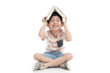 Cute Asian boy with book on head on white background isolated Stock Photo