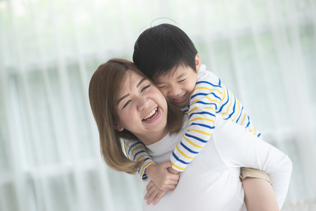 Asian child on a piggy back ride with his mother at home 스톡 콘텐츠
