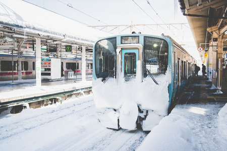 Aomori,Japan, 31 January  2018:Local train on a snowy train station in winter Редакционное