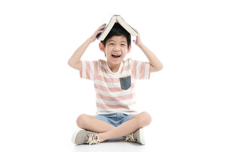 Cute Asian boy with book on head on white background isolated Stockfoto