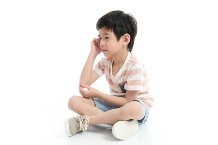 Close up of sad Asian boy sitting on white background isolated