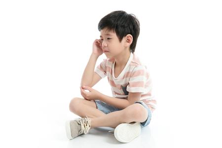 Close up of sad Asian boy sitting on white background isolated
