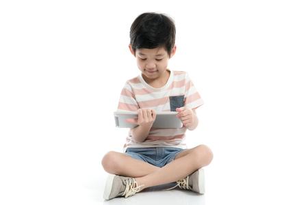Mignon enfant asiatique avec une tablette assis sur fond blanc isolé