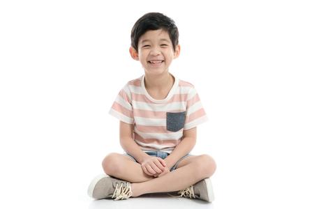 Nettes asiatisches Kind, das auf weißem Hintergrund lokalisiert sitzt