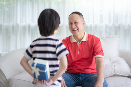 Cute Asian child holding gift box for grand father