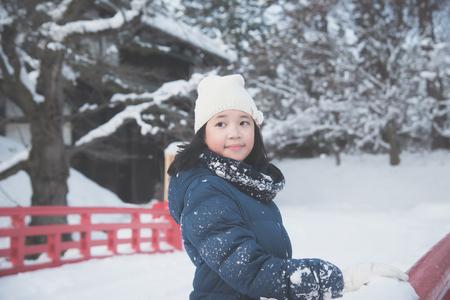 Portrait of beautiful Asian girl on red bridge at Hirosaki Castle in Aomori, Japan