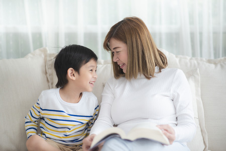 Asian mother Sitting With Son Reading Story together