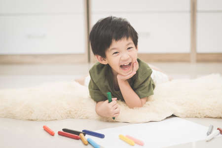 Cute Asian child drawing picture with crayon