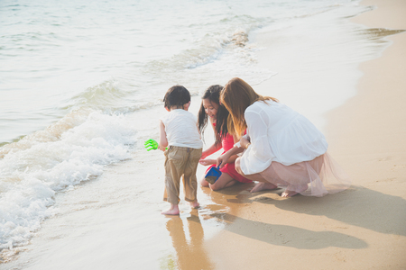 Asian single mom playing with her children on the beach