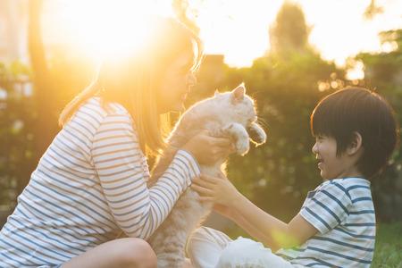 Asiatische Mutter und ihr Sohn spielen mit Katze im Park