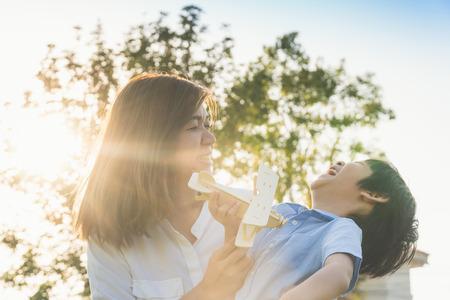 Leuke Aziatische moeder en zoon die samen een houten vliegtuig in het park buiten spelen