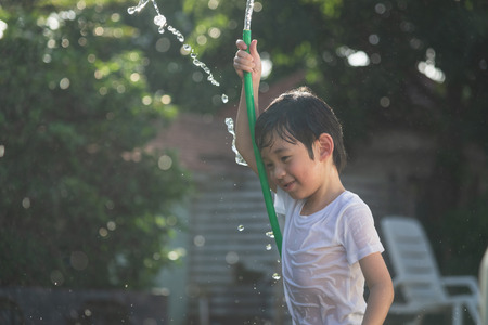 Cute asian boy has fun playing water from a hose in the garden