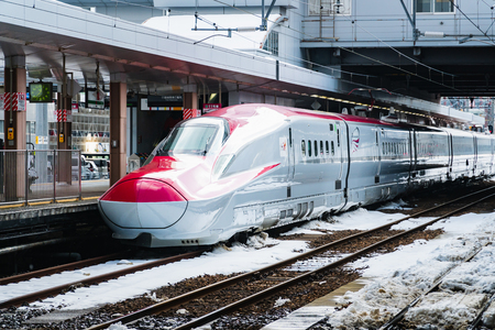 JAN 29, 2019 AKITA, JAPAN : Komachi Super Express Shinkansen E6 series on a snowy train station in winter Редакционное