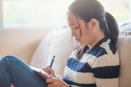 Asian girl drawing picture with digital pen on tablet pc computer while sitting on the couch at home