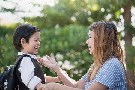 Aziatische moeder neemt afscheid van haar zoon terwijl hij naar school vertrekt, terug naar schoolconcept