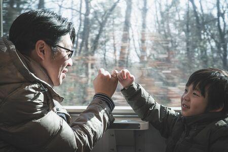 Un padre asiatico e suo figlio fanno una promessa da mignolo mentre viaggiano in treno