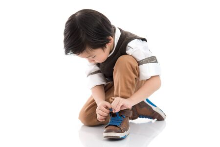 Kleiner asiatischer Junge, der seine Schuhe lokalisiert in weißem Hintergrund bindet Standard-Bild