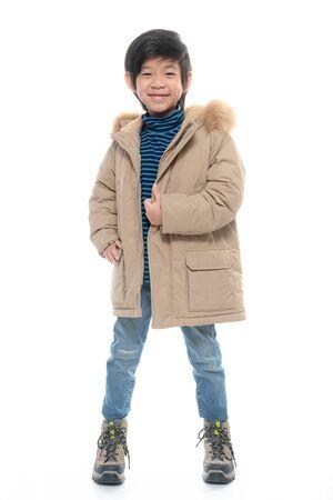 Lindo muchacho asiático en ropa de abrigo sobre fondo blanco aislado. Foto de archivo