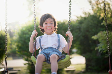 Cute Asian child having fun on swing in the park