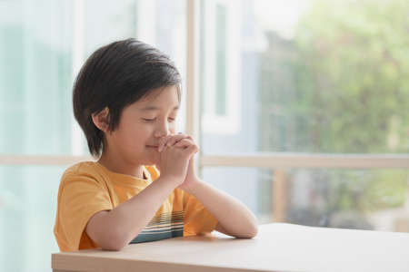 Cute Asian child boy praying with eyes closed in the morning at home