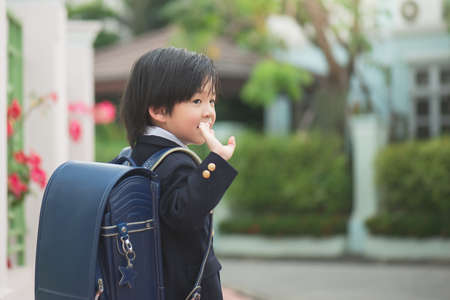 Asian student going to school and waving goodbye,back to school concept,outdoors