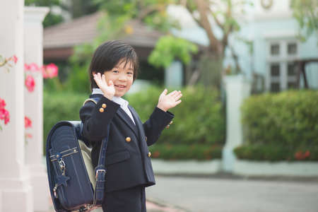 Asian student going to school and waving goodbye,back to school concept,outdoors Archivio Fotografico