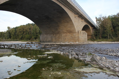 bridge over water: bridge over a river in the mountains in Austria, crystal clear water and stones and rocks Stock Photo