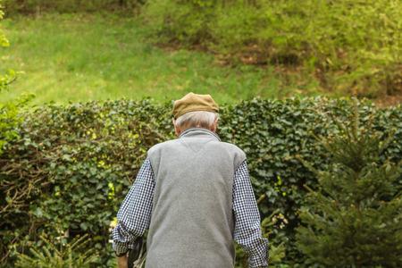 70 80: An older man is walking on the road. He is walking away.
