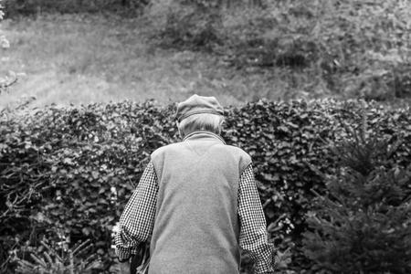 An older man is walking on the road. He is walking away.