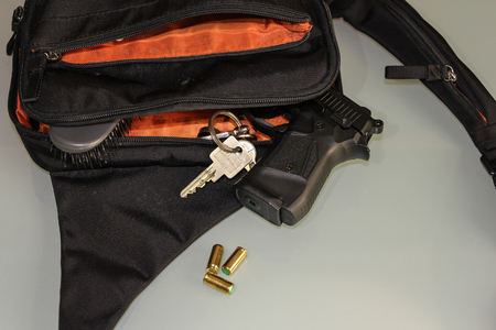 carried: Carried concealed. Handgun and accessories falling from a womans purse.