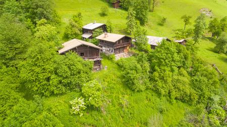 vibrant cottage: Aerial view, Alpine chalets on Green Mountain slope under blue sky. Austria Alps, Salzburg