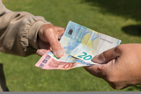 Senior mans hands holding Euro banknote.  pensioners concept.