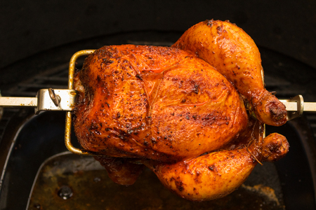 Charred rotisserie chicken over open flames in a barbecue. room for text Stock Photo - 86864502