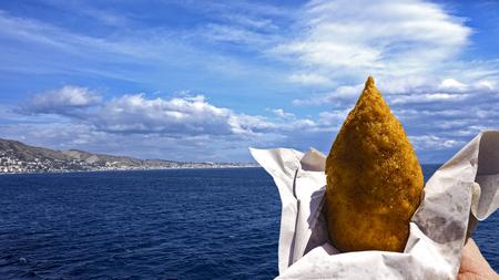 """시실리 60 54의 바다를 생각하는 """"arancino""""를 먹으십시오. 스톡 콘텐츠"""
