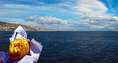 Eat an arancino thinking of the sea of ??sicily 60 Stock Photo