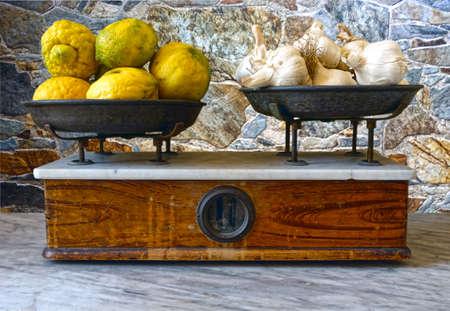 Lemons and garlic bulb on weighing pan - 6859