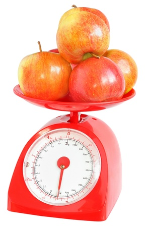 Apples on kitchen scales on a white background.