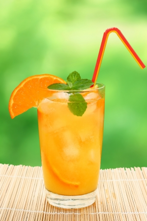 Cocktail with orange juice and ice cubes on a blurred background. photo