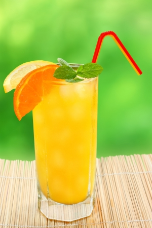 Cocktail with tangerine and lemon juice with ice cubes on a blurred background. photo