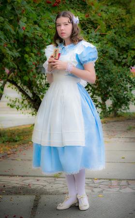 snění: dívka v podobě pohádkové hrdinky v pochybnostech a drží skleněnou lahvičku třešňovou barvu s nálepkou, která mě pila. Reklamní fotografie