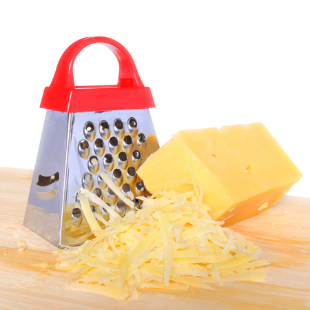 queso rallado: Bar cheese grater and grated cheese on cutting board isolated on a white background