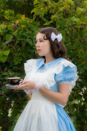 Girl in the garden in the form of fairy-tale heroine holding a couple of tea, going to drink tea. Reklamní fotografie