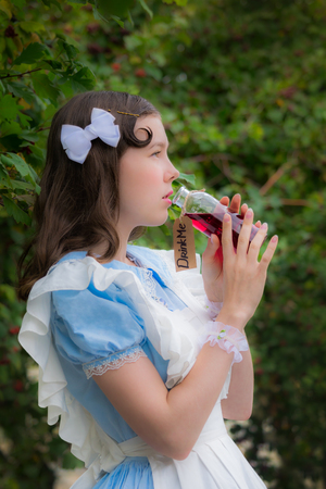 dreaminess: girl in the image of fairy tale heroine drinks the drink of glass bottle cherry color with a label drink me. Stock Photo