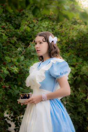 snění: Dívka v podobě báječné hrdinky pije čaj v zahradě. Reklamní fotografie