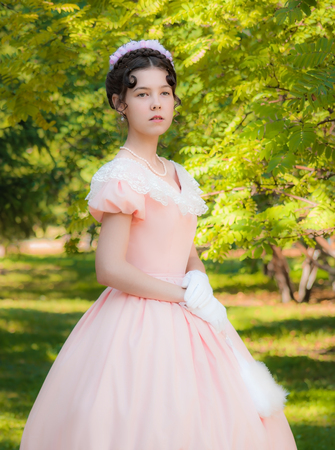 elegance fashion girls look sensuality young: Proud girl in the image of the princess with an attentive look at the outdoors. Stock Photo