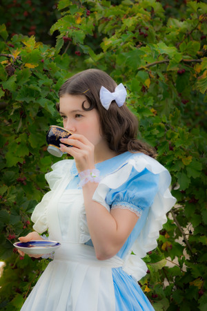 dreaminess: Girl in the image of the fabulous heroine is drinking tea in the garden. Stock Photo