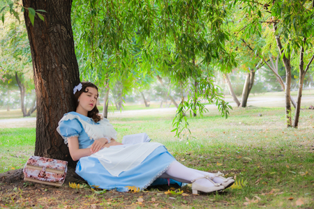 dreaminess: Girl pupil in the image of a character from a fairy tale fell sleep under a tree with a book. Stock Photo